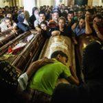 Garoto deita sobre caixões de seus parentes que foram mortos após ataque contra ônibus de cristãos em Minia, no Egito - 26/05/2017 (Ibrahim Ezzat/NurPhoto/Getty Images)